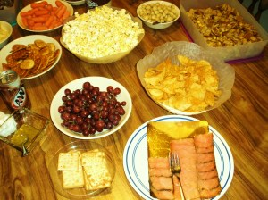 Clockise, from the popcorn: buttered popcorn, seasoned macadamia nuts, randomly put together without a recipe chex mix, Lay`s crab/Bay seasoning chips, lox, Schar table crackers, grapes, dill sauce (for the salmon lox), and some more sodas!