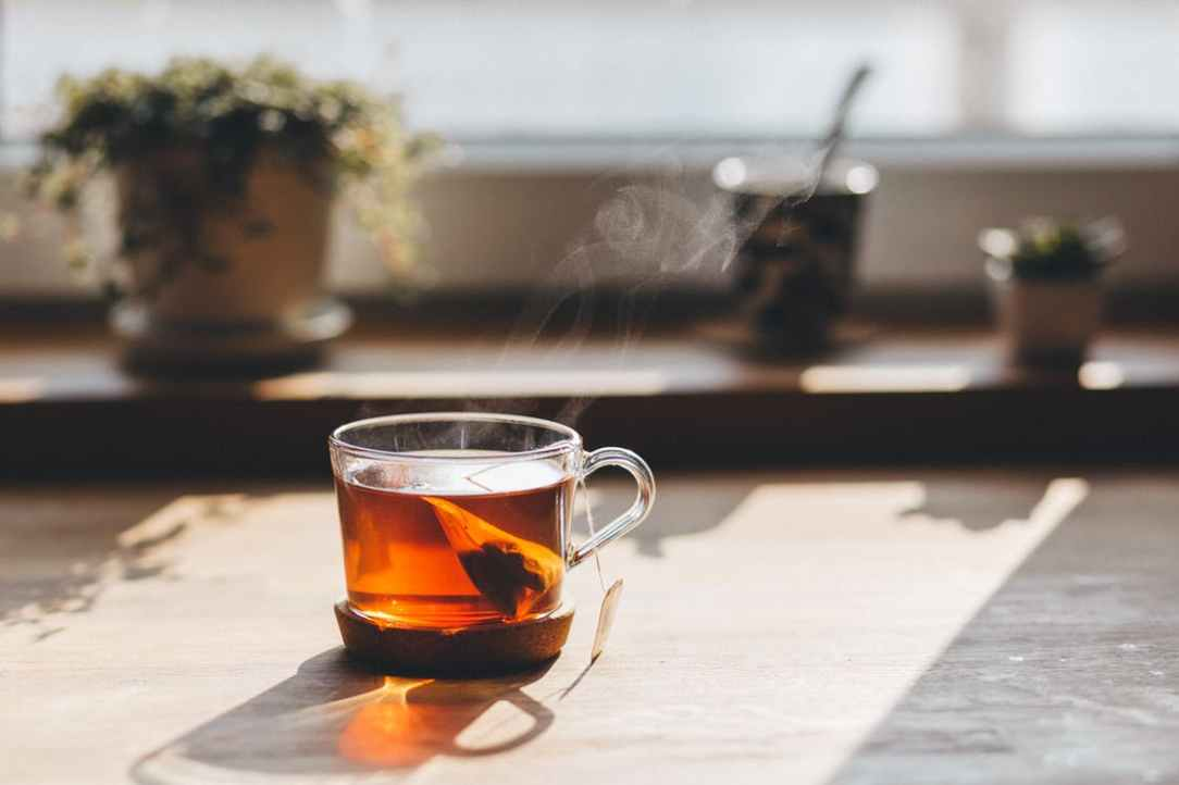 steaming amber cup of tea with teabag in clear mug on cork coaster on stone island countertop in front of counter with out of focus plants at sunny window