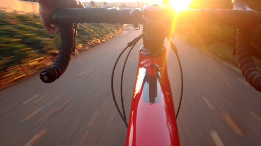 view of sunny road zooming by on asphalt road on red racing road bike